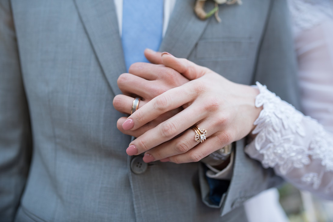 Close up of bride and groom hands and rings