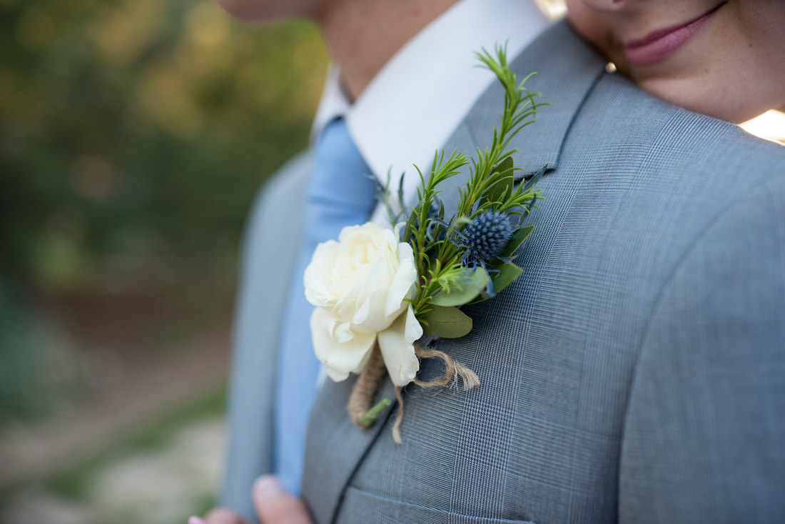 Groom close up boutonniere with thistle and white rose