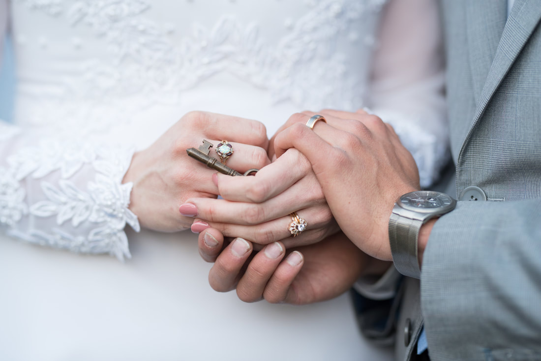 Bride and groom's hands with rings and special gift