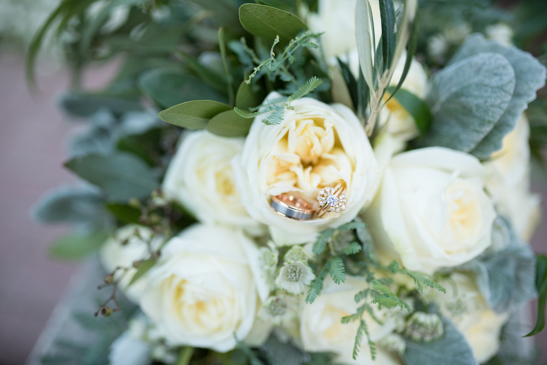 Wedding rings in white rose bouquet