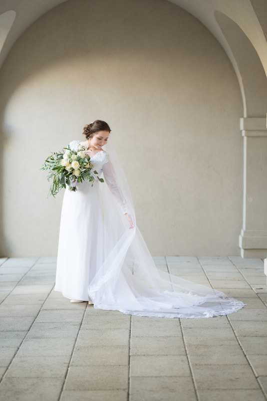 Bride ruffles cathedral veil in full-length portrait
