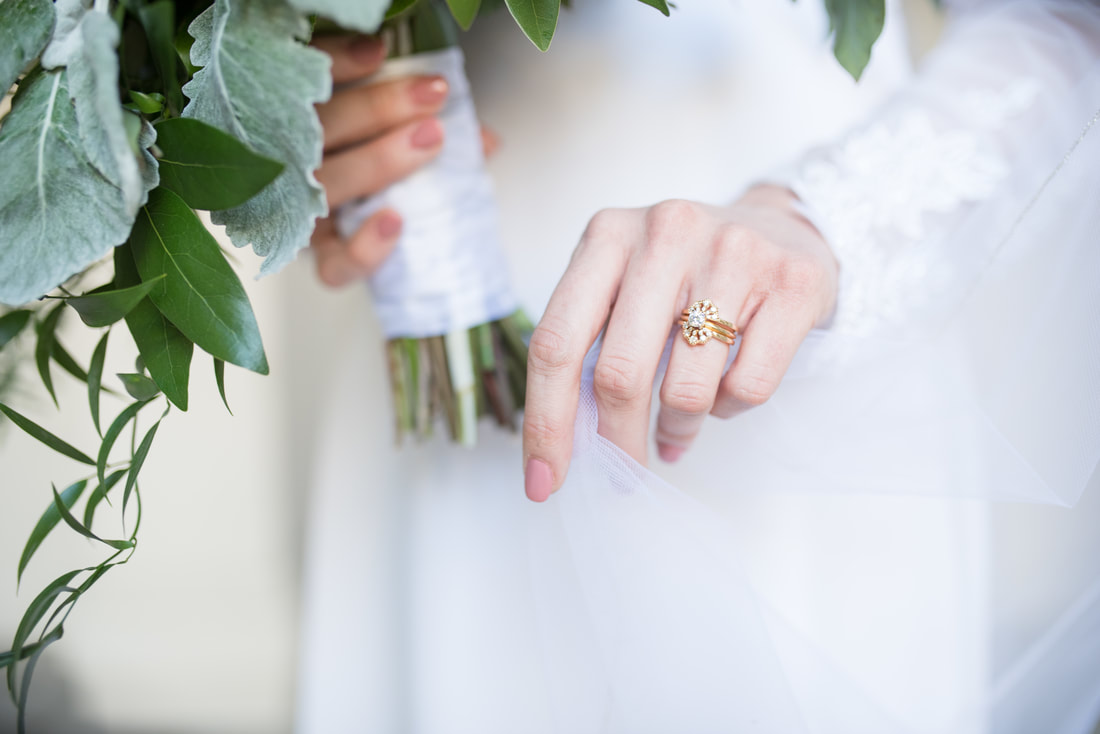Close-up of bride's hand with veil and antique yellow gold wedding ring