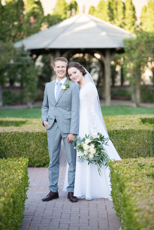 Groom in gray suit and bride in lace gown and long veil with bouquet, standing in the garden at Thanksgiving Point. Bridal session by Flying Gull Photography.