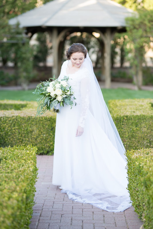 Bride in white lace dress and white lace cathedral veil with white rose bouquet