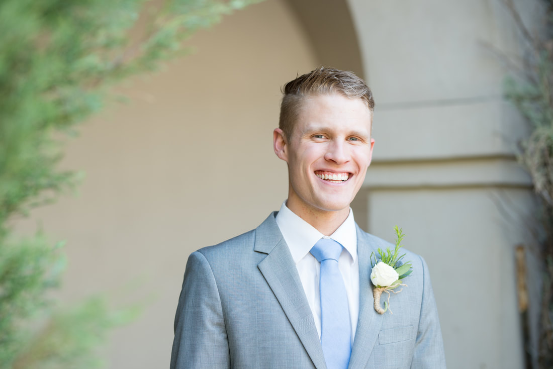 Smiling groom in gray suit at Thanksgiving Point gardens