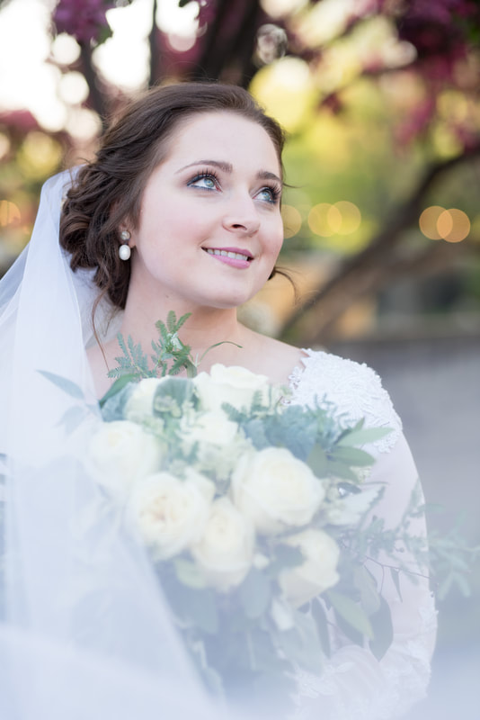 Close-up portrait of bride with flowers in background