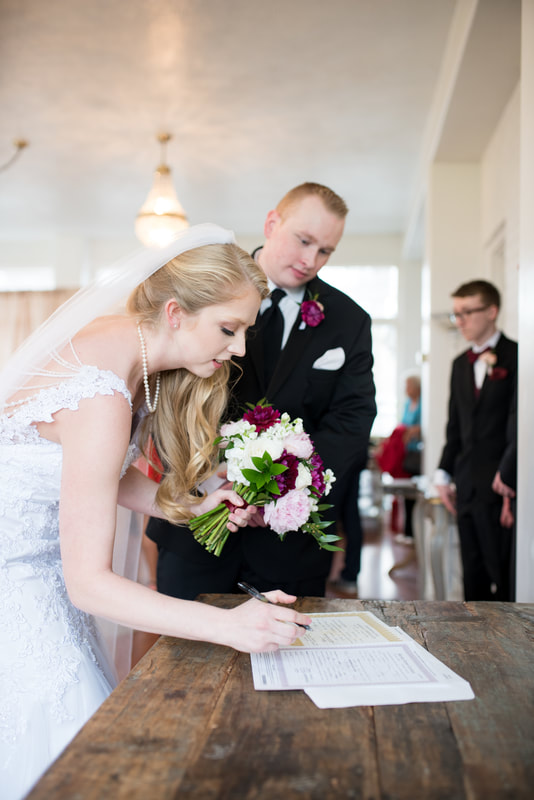 signing the wedding license Traditional wedding and ceremony at Layton, Utah Chantilly Mansion with Flying Gull Photography